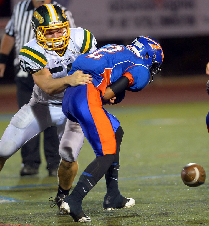 . Canyon High School\'s Ronnie Walker forces a fumble by Andre Baccellia of Westlake High August 30, 2013 in Westlake Village, CA.(Andy Holzman/Los Angeles Daily News)