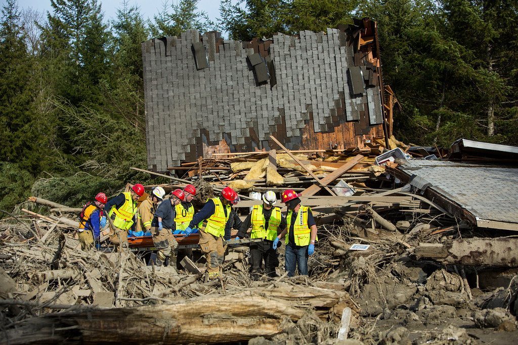 . Rescue workers remove a body from the wreckage of homes destroyed by Saturday\'s mudslide near Oso, Wash, on Monday, March 24, 2014.  (AP Photo/seattlepi.com, Joshua Trujillo)