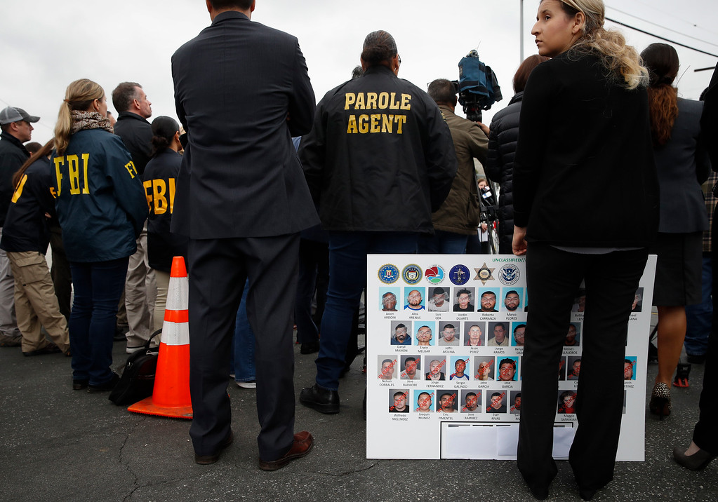 . An FBI employee, who declined to give her name, holds a board showing images of MS-13 gang members during a news conference Wednesday, May 17, 2017, in Los Angeles. Nearly two dozen members and associates of MS-13 were arrested Wednesday morning as hundreds of federal and local law enforcement fanned out across Los Angeles, serving arrest and search warrants. (AP Photo/Jae C. Hong)