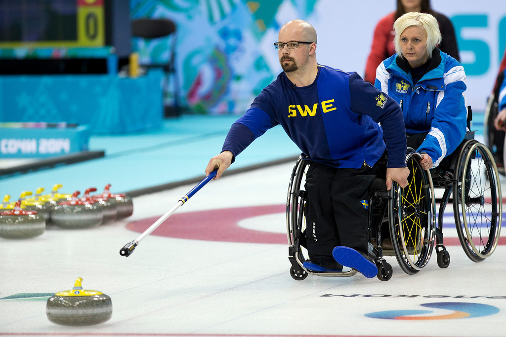. Sweden\'s Kicki Ulander, right, steadies the chair of Patrik Kallin during round robin session wheelchair curling match against Canada at the 2014 Winter Paralympics in Sochi, Russia, Sunday, March 9, 2014. Canada won 7-4. (AP Photo/Pavel Golovkin)