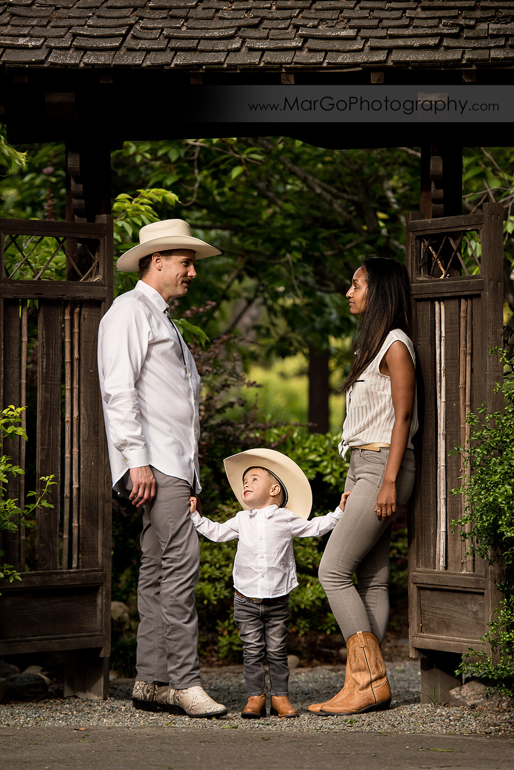 man and little boy in white shirts, gray jeans and cowboy hats and woman in white top standing in wooden gate in Shinn Historical Park and Arboretum in Fremont