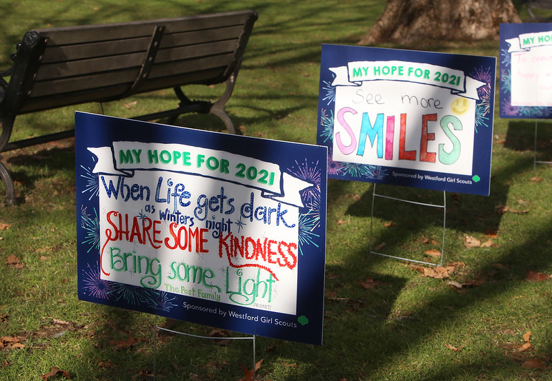 Westford Girl Scout Troop 85009's Signs of Hope project asked community members to sponsor signs on which they wrote their hopes for 2021. The 90 signs are displayed around Westford Town Common until New Year's Day, when the sponsors can come and take their signs home. (SUN/Julia Malakie)