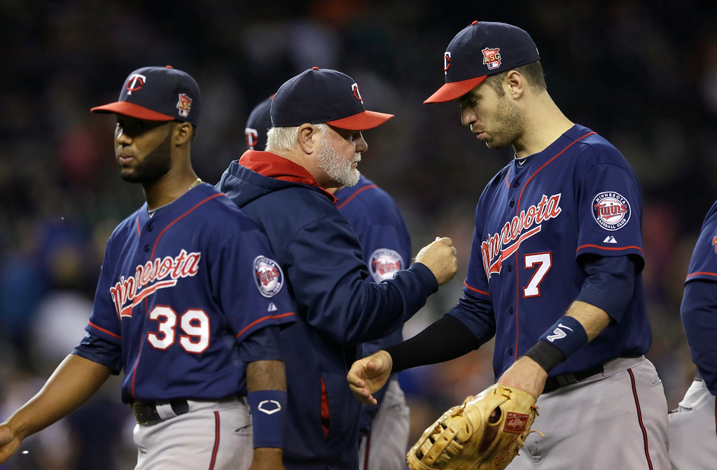 . Minnesota Twins manager Ron Gardenhire, center, greets shortstop Danny Santana (39) and first baseman Joe Mauer (7) after their 12-3 win over the Detroit Tigers in a baseball game in Detroit, Saturday, Sept. 27, 2014. (AP Photo/Carlos Osorio)