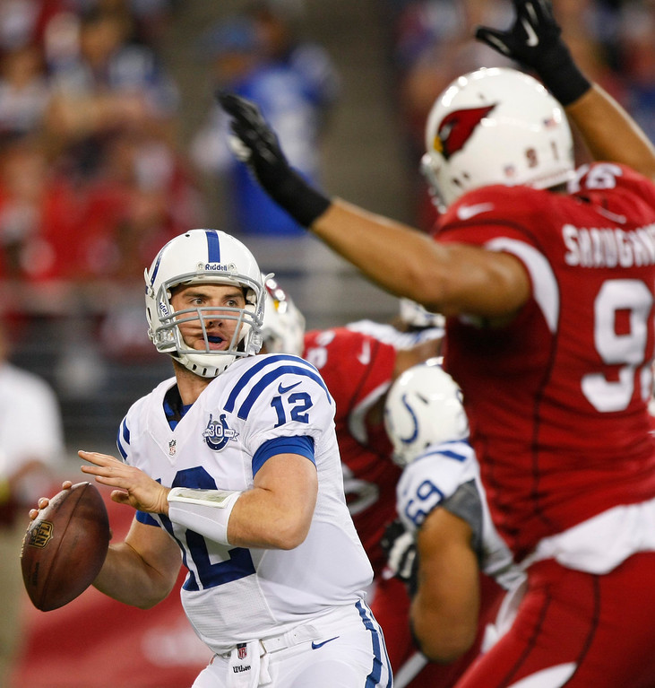 . Indianapolis Colts quarterback Andrew Luck (12) throws under pressure from Arizona Cardinals outside linebacker Matt Shaughnessy (91) during the first half of an NFL football game, Sunday, Nov. 24, 2013, in Glendale, Ariz. (AP Photo/Rick Scuteri)