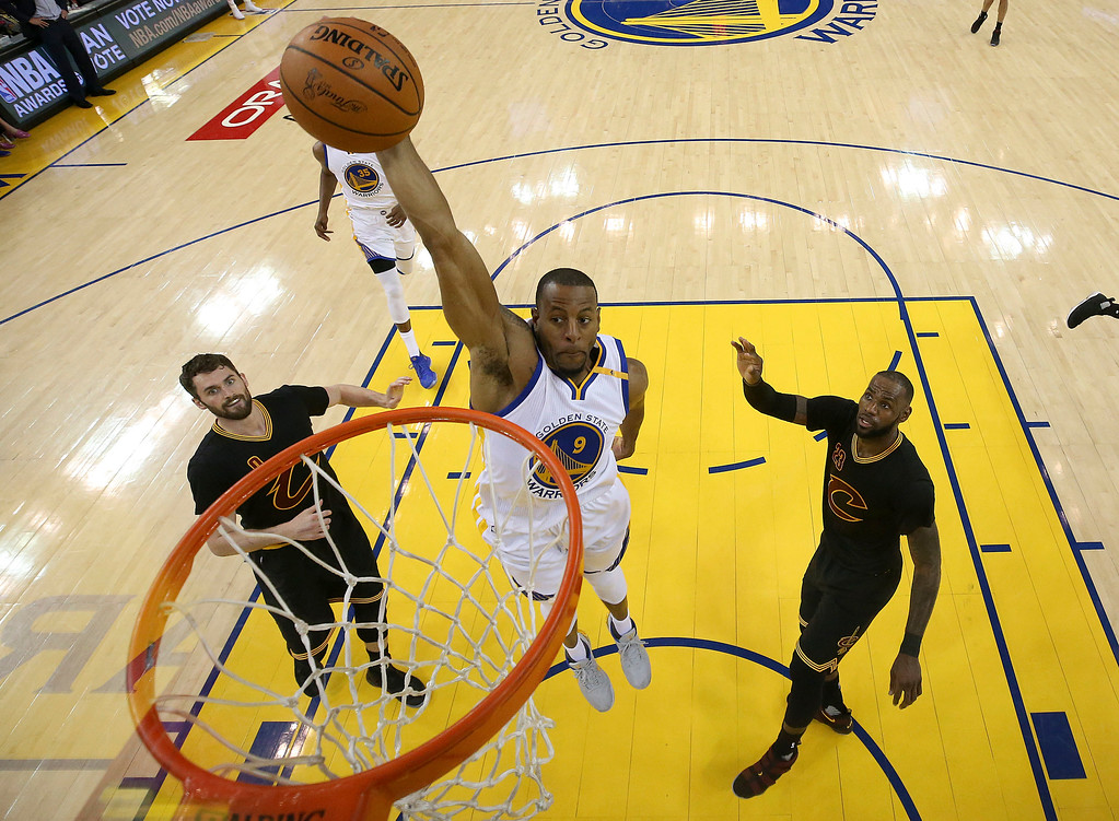 . Golden State Warriors forward Andre Iguodala (9) dunks between Cleveland Cavaliers forward Kevin Love (0) and forward LeBron James (23) during the first half of Game 5 of basketball\'s NBA Finals in Oakland, Calif., Monday, June 12, 2017. (Ezra Shaw/Pool Photo via AP)