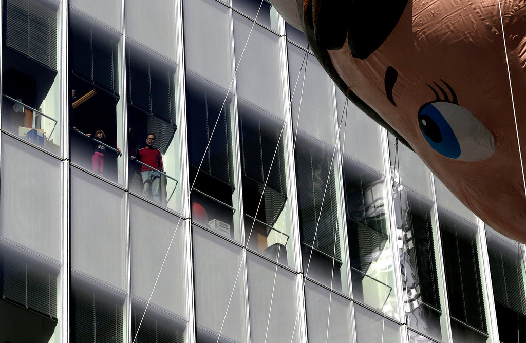 ". People look out of a window of a building as the ""Elf-in-a-Shelf \""balloon flies by during the Macy\'s Thanksgiving Day Parade, Thursday, Nov. 28, 2013, in New York. After fears the balloons could be grounded if sustained winds exceeded 23 mph, Snoopy, Spider-Man and the rest of the iconic balloons received the all-clear from the New York Police Department to fly between Manhattan skyscrapers on Thursday. (AP Photo/Julio Cortez)"