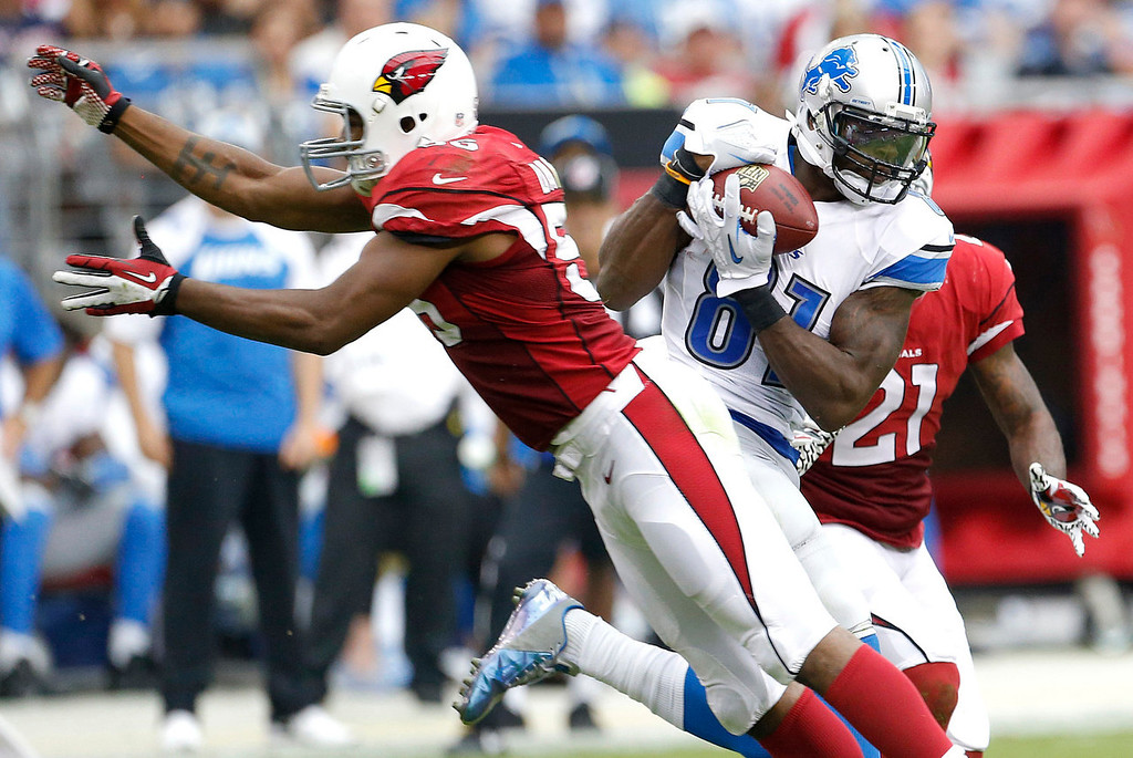 . Detroit Lions wide receiver Calvin Johnson (81) pulls in a pass and runs in for a touchdown as Arizona Cardinals cornerback Patrick Peterson (21) and Karlos Dansby (56) defend during the first half of a NFL football game, Sunday, Sept. 15, 2013, in Glendale, Ariz. (AP Photo/Darryl Webb)