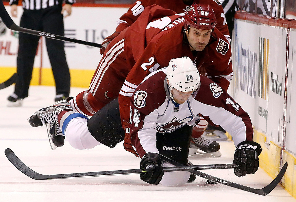 . Colorado Avalanche\'s Marc-Andre Cliche, bottom, gets taken down by Phoenix Coyotes\' Kyle Chipchura during the second period of an NHL hockey game Thursday, Nov. 21, 2013, in Glendale, Ariz. (AP Photo/Ross D. Franklin)
