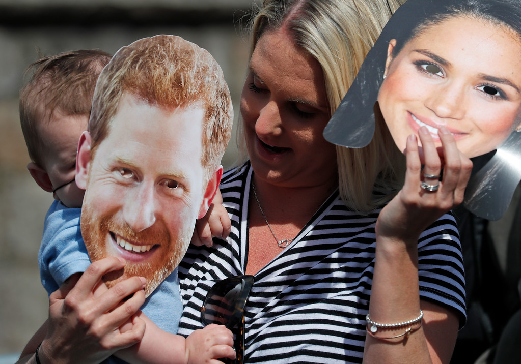 . A royal fan puts on masks in Windsor, Friday, May 18, 2018. Preparations are being made in the town ahead of the wedding of Britain\'s Prince Harry and Meghan Markle that will take place in Windsor on Saturday May 19.(AP Photo/Frank Augstein)