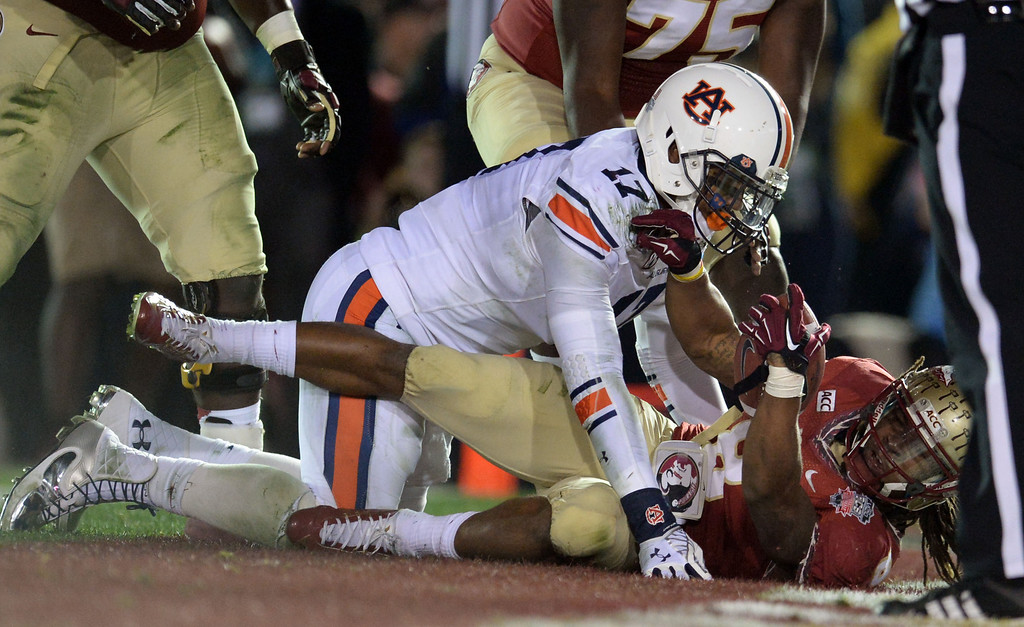 . Florida State running back Devonta Freeman (8) dives a touchdown past Auburn linebacker Kris Frost (17) in the first half of the BCS National Championship game at the Rose Bowl in Pasadena, Calif., on Monday, Jan. 6, 2014. 