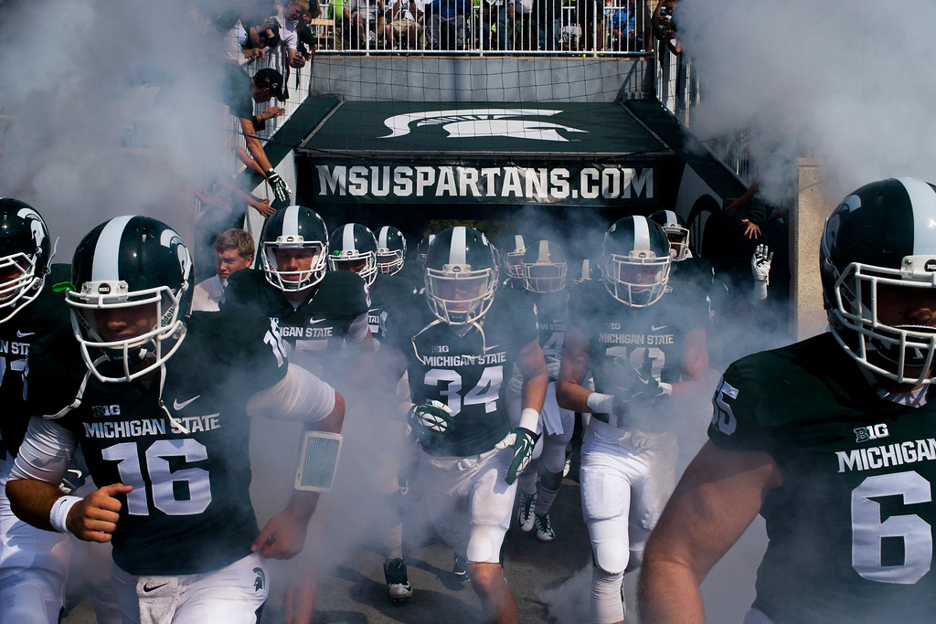 . Michigan State\'s Tommy Vento, left, runs alongside his teammates as they take the field through a screen of smoke before playing Eastern Michigan on Saturday, Sept. 20, 2014 at Spartan Stadium in East Lansing, Mich. (AP Photo/The Flint Journal, Jake May)