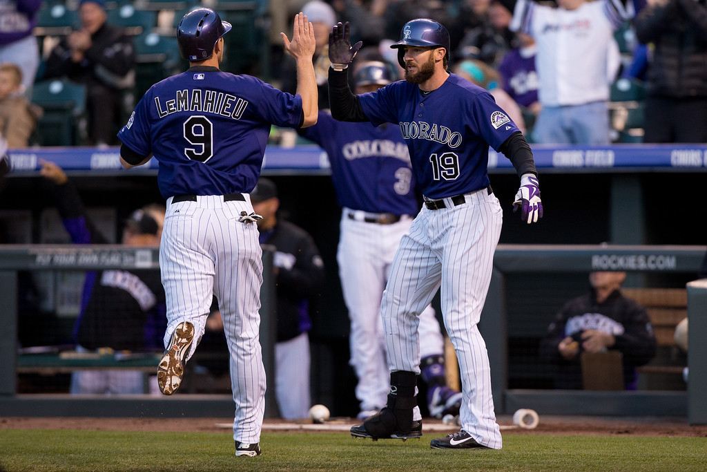 . DJ LeMahieu #9 of the Colorado Rockies celebrates with teammate Charlie Blackmon #19 after scoring on a double by Justin Morneau #33 (not pictured) during the second inning against the Chicago White Sox at Coors Field on April 7, 2014 in Denver, Colorado. (Photo by Justin Edmonds/Getty Images)