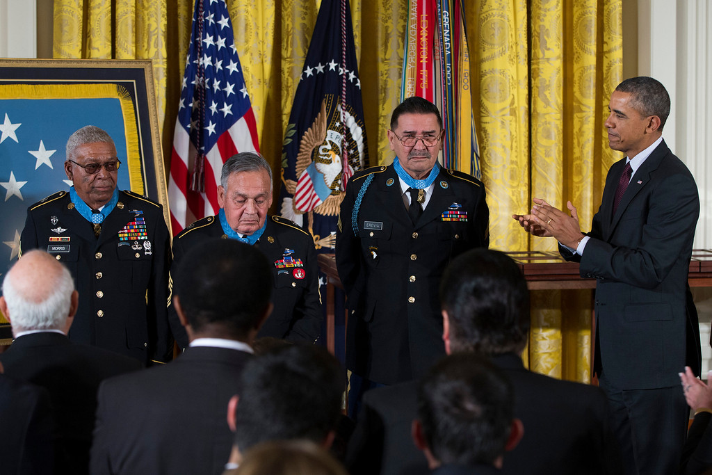 . President Barack Obama applauds, from left, Staff Sgt. Melvin Morris, Sgt. 1st Class Jose Rodela, and Spc. Santiago J. Erevia after he awarded them with the Medal of Honor during a ceremony in the East Room of the White House in Washington, Tuesday, March 18, 2014. President Obama awarded 24 Army veterans the Medal of Honor for conspicuous gallantry in recognition of their valor during major combat operations in World War II, the Korean War and the Vietnam War. (AP Photo/ Evan Vucci)