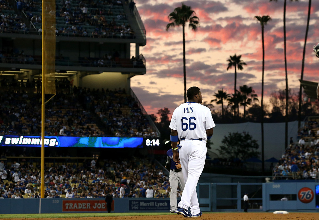 . LOS ANGELES, CA - JULY 12:   Yasiel Puig #66 of the Los Angeles Dodgers walks to take his positon after grounding out to end the third inning against the Colorado Rockies at Dodger Stadium on July 12, 2013 in Los Angeles, California.  (Photo by Stephen Dunn/Getty Images)
