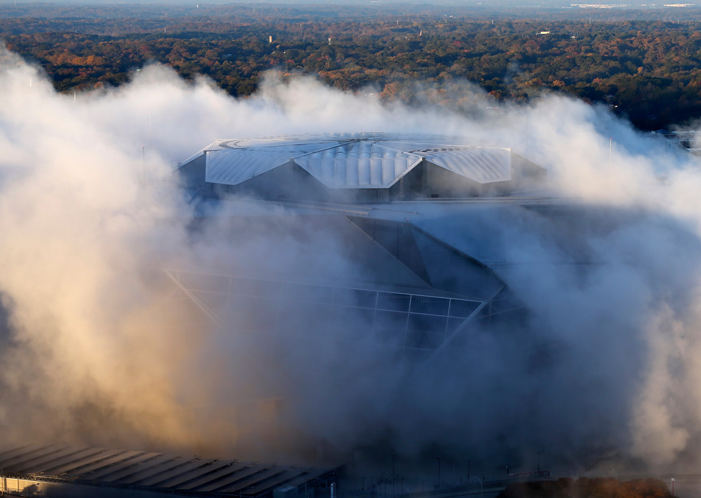 . A dust cloud engulfs the Mercedes-Benz Stadium following the implosion of the Georgia Dome, which was next door to the stadium, Monday, Nov. 20, 2017, in Atlanta. The Dome was the home of the Atlanta Falcons, hosted Super Bowls and the 1996 Summer Olympic Games among other sporting events. (AP Photo/John Bazemore)