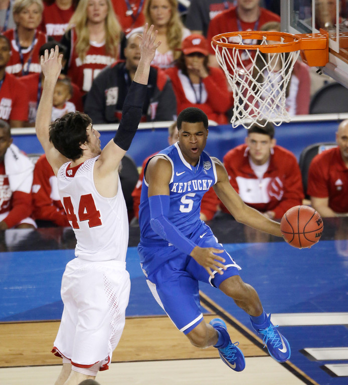 . Kentucky guard Andrew Harrison, right, drives past Wisconsin forward Frank Kaminsky, left, during the first half of an NCAA Final Four tournament college basketball semifinal game Saturday, April 5, 2014, in Arlington, Texas. (AP Photo/Tony Gutierrez)