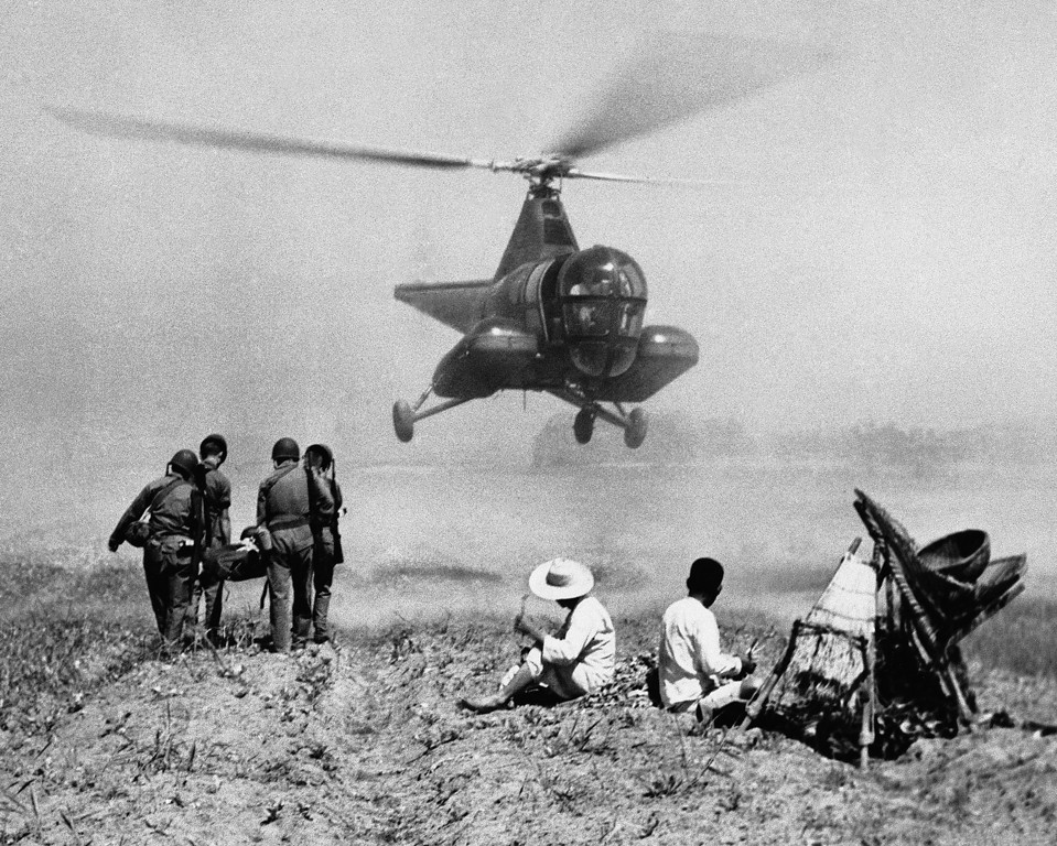 . Even though \'Armistice\' talks are in progress at Kaesong, the mission of the 3rd Air Rescue Squadron continues. 3rd Air Rescue Helicopter as it settles, gently to Korean soil to take on an injured soldier being carried in a stretcher by medics on July 7, 1951.   In a matter of minutes this soldier will be under the professional care of a medical officer at one of the mobile army surgical hospitals at the rear.  Two Korean Laborers have stacked their \'A\' frames to watch the patient loaded into the helicopters capsules. More than 2300 lives have been saved by Air Rescue personnel who are serving the Far East Air Forces during the Korean War.  This number represents rescues made by all the 3rd Rescue Aircraft. (AP Photo)