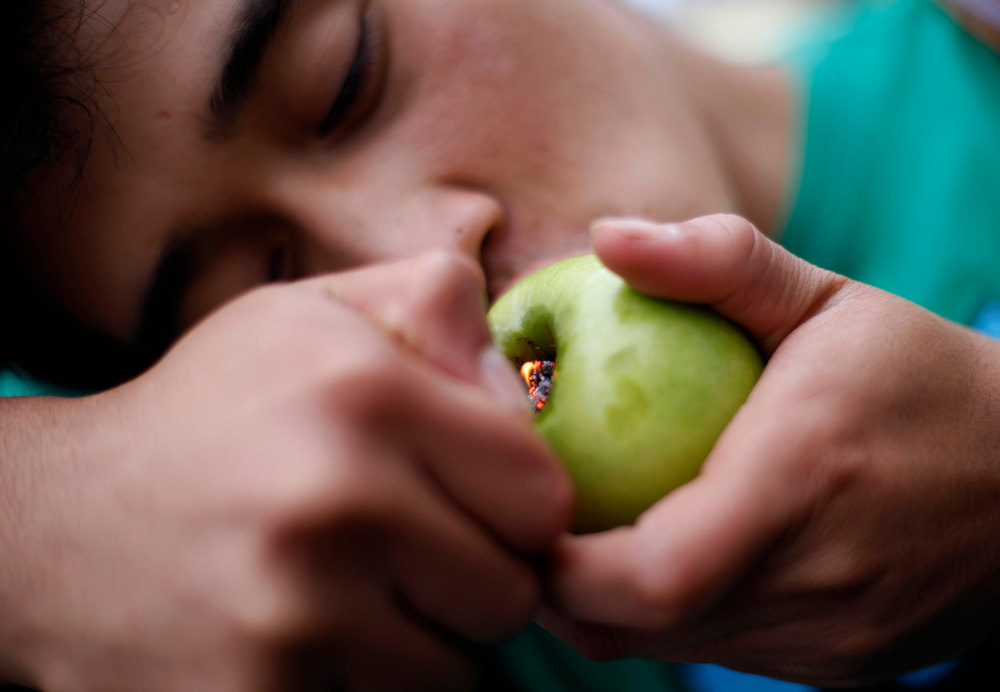 Description of . A man smokes marijuana using an apple adapted with a pipe during a demonstration calling for the legalisation of the drug in Guatemala City November 24, 2012.       REUTERS/Jorge Dan Lopez