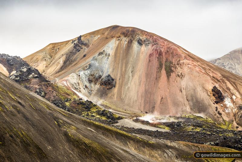 Walkers explore the geothermal vents and sulphur fumaroles near Brennisteinsalda, Landmannalaugar