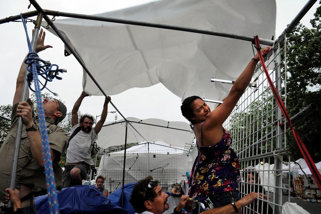 . Carolina Wright, right,  joins other pedestrians struggling to dismantle a vendors tent at the annual Capitol Hill People\'s Fair as high winds and stormy weather moved into downtown Denver, CO, Saturday June 2, 2012.  A Special Weather Statement warned of heavy thunderstorms from north of Denver down to south of Colorado Springs and hail was reported in the Parker area. Craig F. Walker, The Denver Post