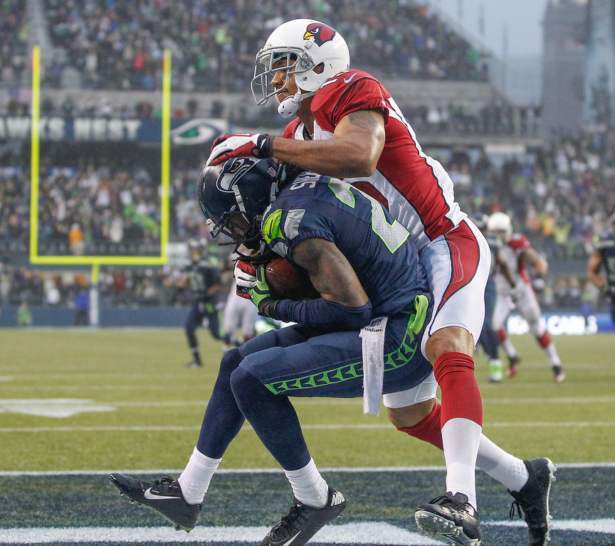 . Cornerback Richard Sherman #25 of the Seattle Seahawks intercepts a pass in the end zone against Michael Floyd #15 of the Arizona Cardinals at CenturyLink Field on December 22, 2013 in Seattle, Washington. The Cardinals defeated the Seahawks 17-10.  (Photo by Otto Greule Jr/Getty Images)