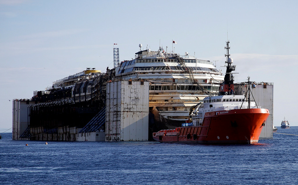 . The Costa Concordia cruise wreck is maneuvered into position to be towed away from the tiny Tuscan island of Isola del Giglio, Italy, Wednesday, July 23, 2014.  After more than two years since it slammed into a reef along the coastline of Isola del Giglio the wreck has begun its last journey, to the Italian port of Genoa, where it will be scrapped. 32 people died in the incident. (AP Photo/Gregorio Borgia)