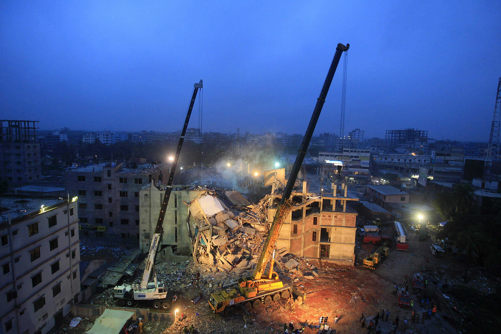 . Cranes operated by Bangladeshi Army personnel work at the scene of the April 24 collapse of an eight-story building in Savar, on the outskirts of Dhaka, on April 29, 2013.  Bangladeshi textile bosses pleaded April 29 with Western clothing giants to keep doing business with them after nearly 400 people died in a factory collapse as hopes of finding more survivors faded. The factory caved in while some 3,000 textile workers were on shift.  STRDEL/AFP/Getty Images