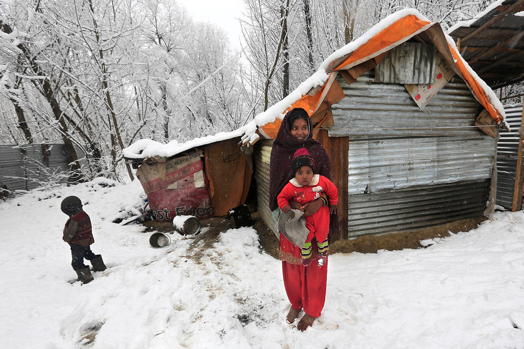 . An Indian woman laborer holds her son as they watch fresh snow in Srinagar, India, Tuesday, Dec. 31, 2013. Snowfall in the Indian portion of Kashmir has disrupted power supply, air traffic and road traffic between Srinagar and Jammu, the summer and winter capitals of India\'s Jammu-Kashmir state, according to news reports. (AP Photo/Dar Yasin)