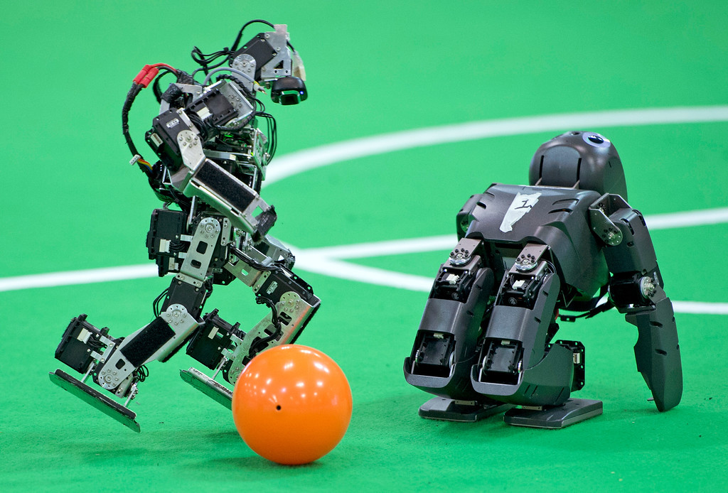 . A robot of a German team, left, plays the ball besides a British team robot in the Kids League at the RoboCup German Open 2014 in Magdeburg, Germany, Thursday, April 3, 2014. 44 international RoboCup Major League teams from 12 countries demonstrate the state-of-the-art competitions in soccer, rescue and service robots. The RoboCup German Open takes place from April 3 to April 5, 2014. (AP Photo/Jens Meyer)
