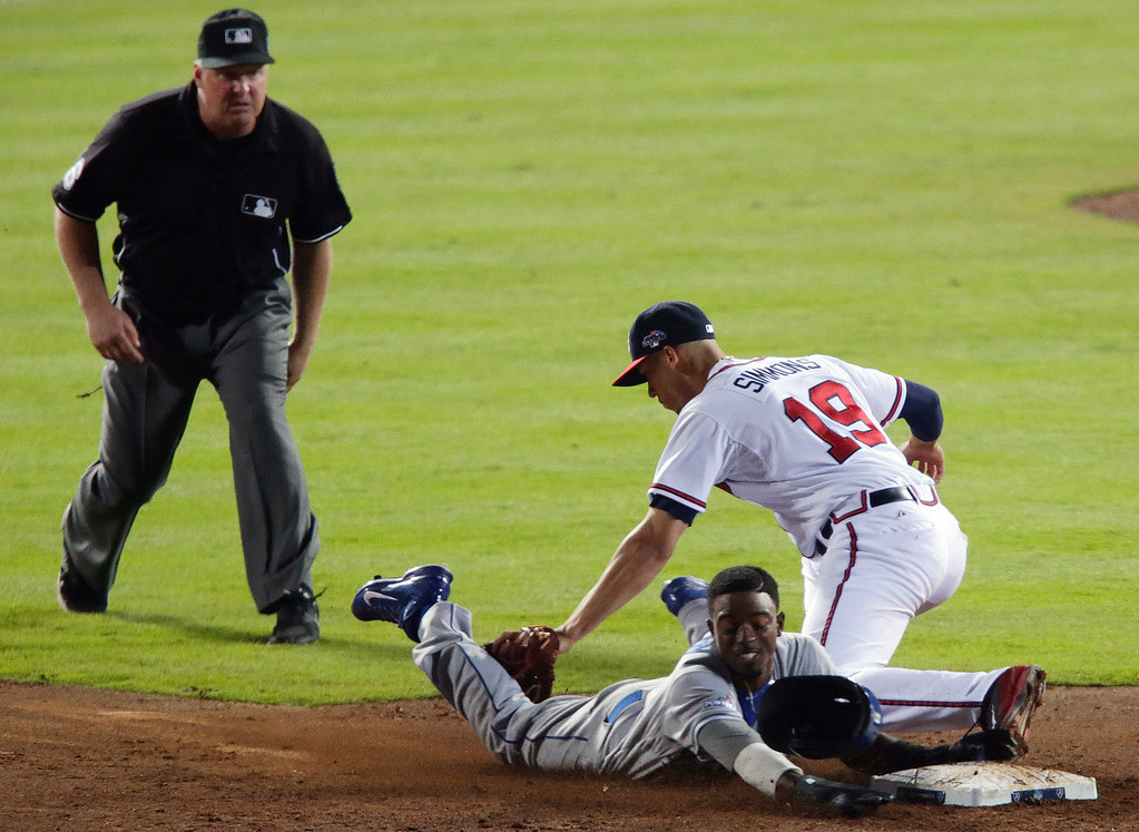. As umpire Mike Muchlinski, left, watches, Los Angeles Dodgers\' Dee Gordon, bottom right, tries to steal second base as Atlanta Braves shortstop Andrelton Simmons (19) makes the tag in the ninth inning of Game 2 of the National League division series on Friday, Oct. 4, 2013, in Atlanta. The Braves won 4-3. (AP Photo/Dave Martin)