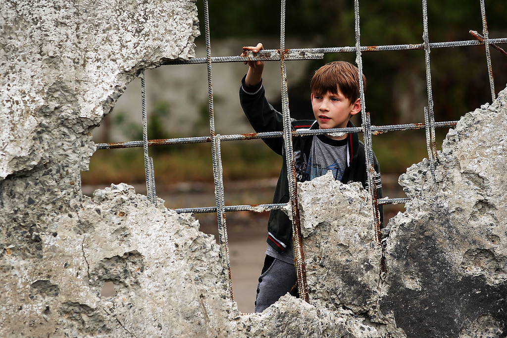 . ALOVAISK, UKRAINE - SEPTEMBER 10: A boy looks out from a wall damaged during heavy fighting on September 10, 2014 in Alovaisk, Ukraine. Alovaisk, which is about an hour outside of the separatist held city of Donetsk, saw sustained shelling in August and is still the site of fighting between Ukrainian troops and the Russian backed separatists.  (Photo by Spencer Platt/Getty Images)