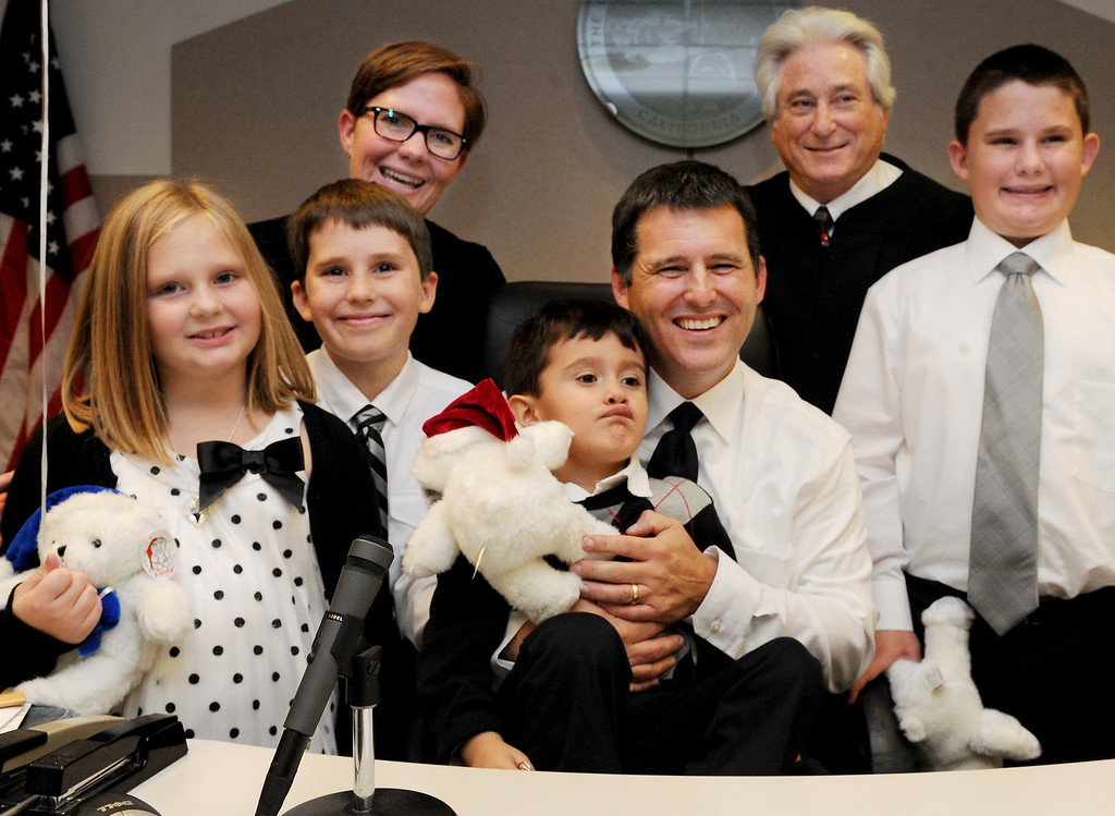 . Anna Adam, Kerry, Angel, John and Adam Rigby pose for a photo with Judge Michael Nash after John and Kerry Rigsby adopted Angel. On National Adoption Day, hundreds of courts and organizations throughout the nation open their doors to finalize adoptions of children in foster care. Nintey-Five families celebrate with their newly adopted children at the Edmund D. Edelman Children\'s Court in Monterey Park Friday, November 22, 2013.(Photo by Walt Mancini/Los Angeles Daily News)