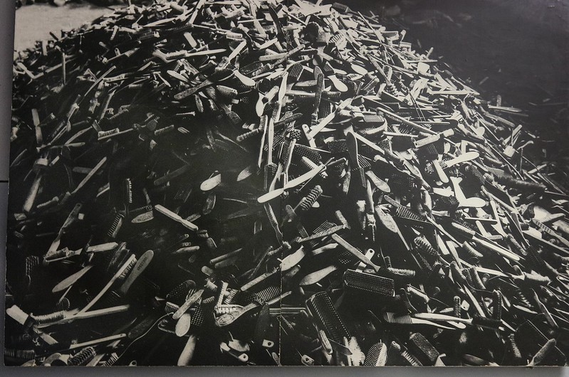 Piles of confiscated hair and tooth brushes, taken from victims. Photo of a period photo.