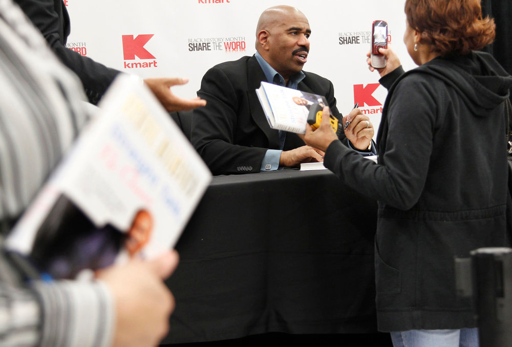 Description of . Steve Harvey, comedian and TV personality, center, signs copies of his latest book,