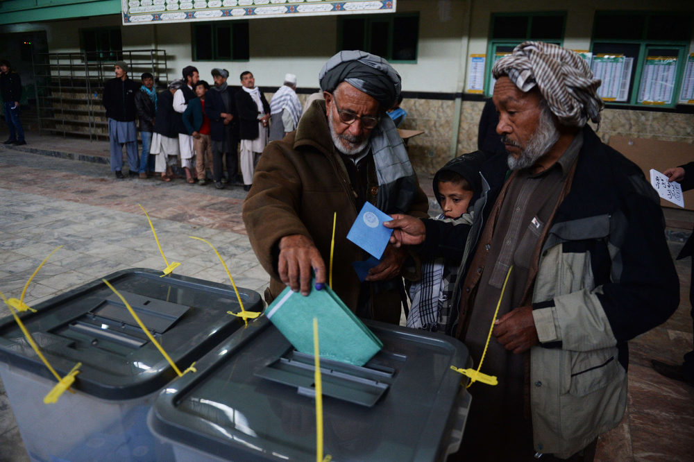 . An elderly Afghan voter casts his ballot at a local polling station in Kabul on April 5, 2014. Afghan voters went to the polls to choose a successor to President Hamid Karzai, braving Taliban threats in a landmark election held as US-led forces wind down their long intervention in the country. Afghanistan\'s third presidential election brings an end to 13 years of rule by Karzai, who has held power since the Taliban were ousted in a US-led invasion in 2001, and will be the first democratic handover of power in the country\'s turbulent history.   (SHAH MARAI/AFP/Getty Images)