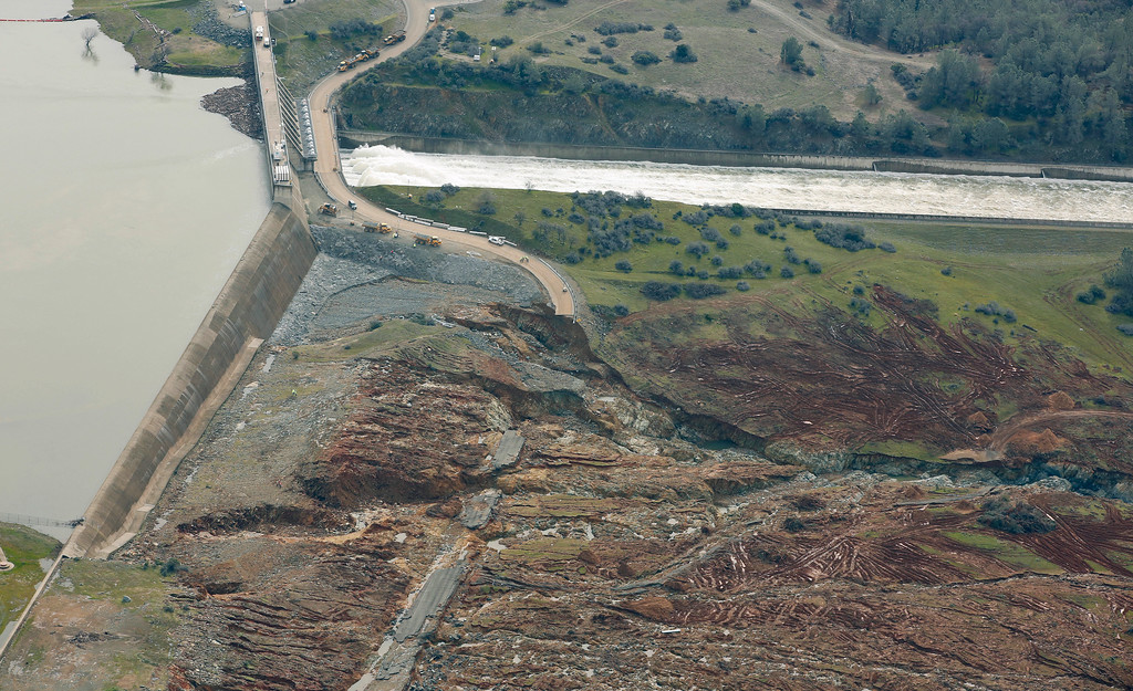 . Erosion caused when overflow water cascaded down the emergency spillway, bottom, is seen as water continues to flow down the main spillway, top, of the Oroville Dam, Monday, Feb. 13, 2017, in Oroville, Calif. The water level dropped Monday at the nation\'s tallest dam easing slightly the fears of a catastrophic spillway collapse that prompted authorities to order people to leave their homes downstream. (AP Photo/Rich Pedroncelli)