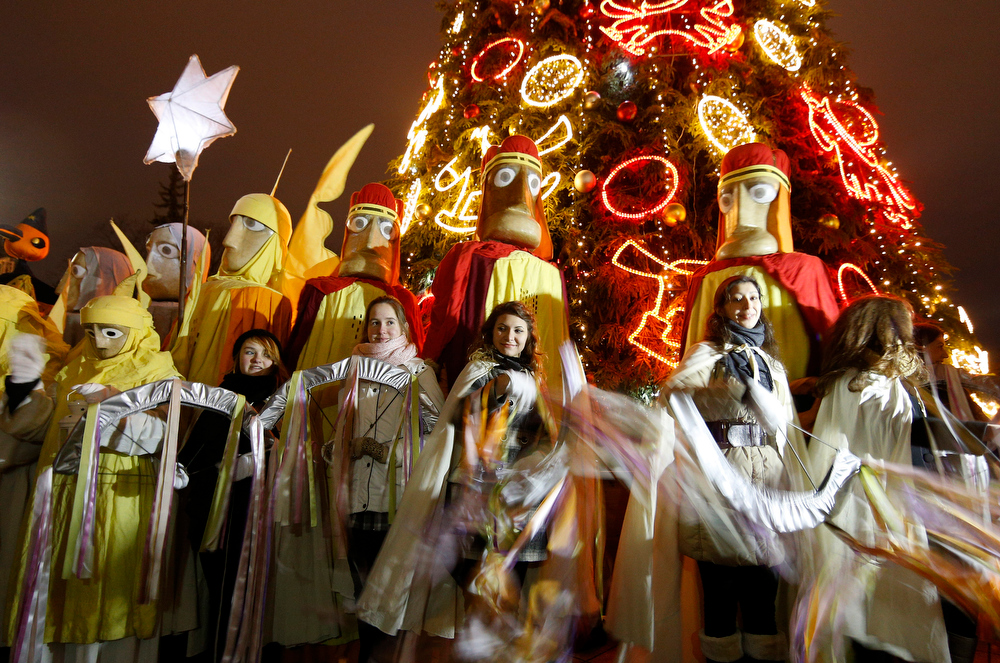. Lithuanians dressed as the Three Kings, pause in the street, during the Epiphany Day celebrations in downtown Vilnius, Lithuania, Monday, Jan. 6, 2014. Epiphany, the 12th night of Christmas, marks the day the three wise men visited Christ. (AP Photo/Mindaugas Kulbis)