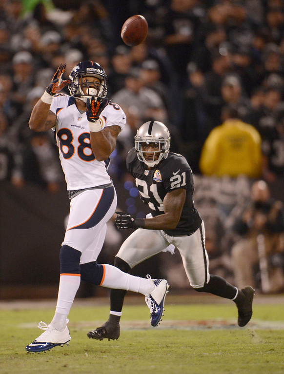 . Denver Broncos wide receiver Demaryius Thomas (88) catches a pass on Oakland Raiders cornerback Ron Bartell (21) during the first quarter Thursday, December 6, 2012 during Thursday Night Football at O.c Coliseum in Oakland  John Leyba, The Denver Post