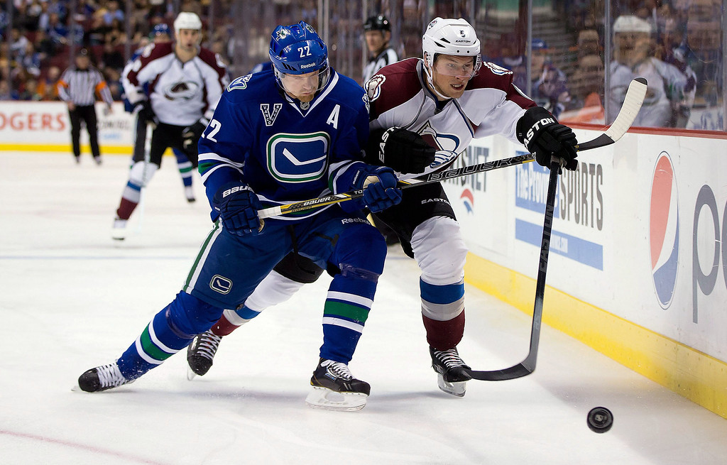 . Vancouver Canucks\' Daniel Sedin, left, of Sweden, checks Colorado Avalanche\'s Erik Johnson during the first period of an NHL hockey game in Vancouver, British Columbia, Thursday, March 28, 2013. (AP Photo/The Canadian Press, Darryl Dyck)