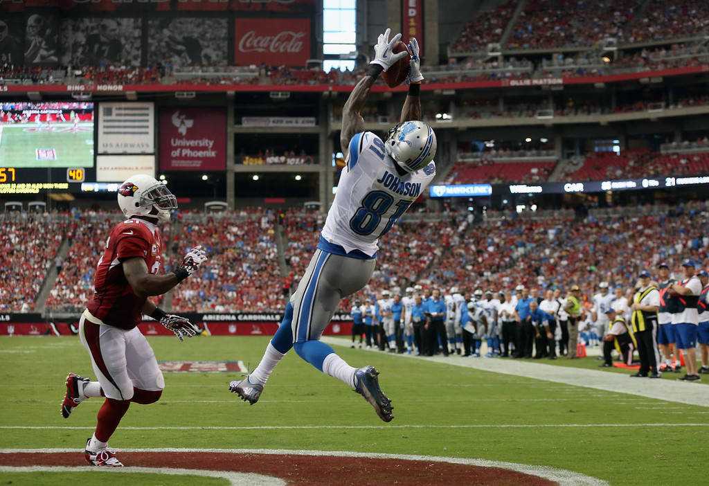 . Wide receiver Calvin Johnson #81 of the Detroit Lions catches a touchdown pass in front of cornerback Patrick Peterson #21 of the Arizona Cardinals in the first half at University of Phoenix Stadium on September 15, 2013 in Glendale, Arizona.  (Photo by Jeff Gross/Getty Images)