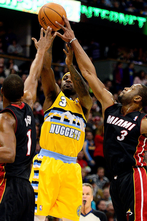 . Dwyane Wade (3) of the Miami Heat blocks a shot as Chris Bosh (1) of the Miami Heat  defends as Ty Lawson (3) of the Denver Nuggets shoots during the first half of action.    (Photo by AAron Ontiveroz/The Denver Post)