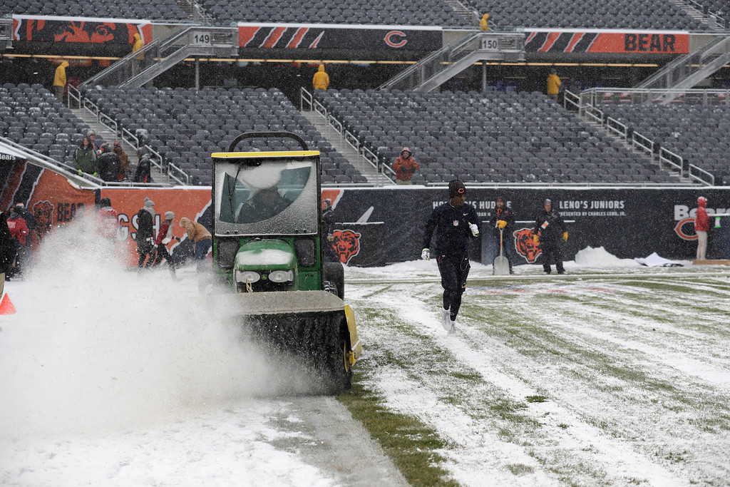 . Workers clear snow from Soldier Field before an NFL football game between the Chicago Bears and Cleveland Browns in Chicago, Sunday, Dec. 24, 2017. (AP Photo/Nam Y. Huh)