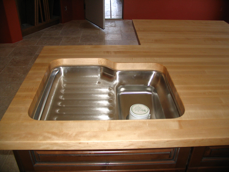 Prep sink installed in the butcher block countertop on the island in the kitchen.