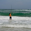 Man surf fishing, casting into the ruff ocean.