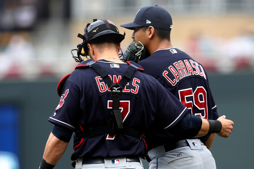 . Cleveland Indians pitcher Carlos Carrasco, right, gets some encouragement from catcher Yan Gomes with the bases loaded by the Minnesota Twins in the first inning of the first game of a baseball doubleheader Thursday, Aug. 17, 2017, in Minneapolis. The Twins left the inning with the bases loaded. (AP Photo/Jim Mone)