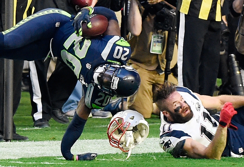 . Jeremy Lane #20 of the Seattle Seahawks breaks his arm after an interception as he is tackled by Julian Edelman #11 of the New England Patriots in the first quarter during Super Bowl XLIX at University of Phoenix Stadium on February 1, 2015 in Glendale, Arizona.  (Photo by Harry How/Getty Images)