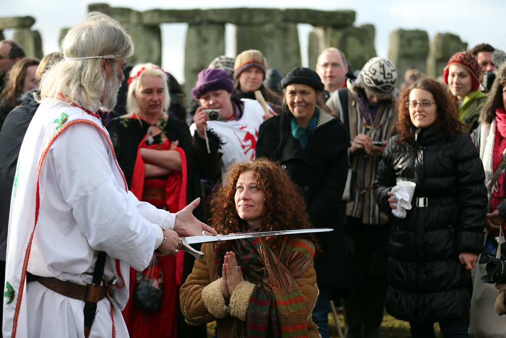 Description of . Arthur Uther Pendragon (L) knights a woman as Druids conduct a ceremony following the traditional winter solstice celebrations at Stonehenge to coincide with the supposed Mayan Apocalypse, on December 21, 2012 in Wiltshire, England. Predictions that the world will end today as it marks the end of a 5,125-year-long cycle in the ancient Maya calendar, encouraged a larger than normal crowd to gather at the famous historic stone circle to celebrate the sunrise closest to the Winter Solstice, the shortest day of the year.  (Photo by Matt Cardy/Getty Images)