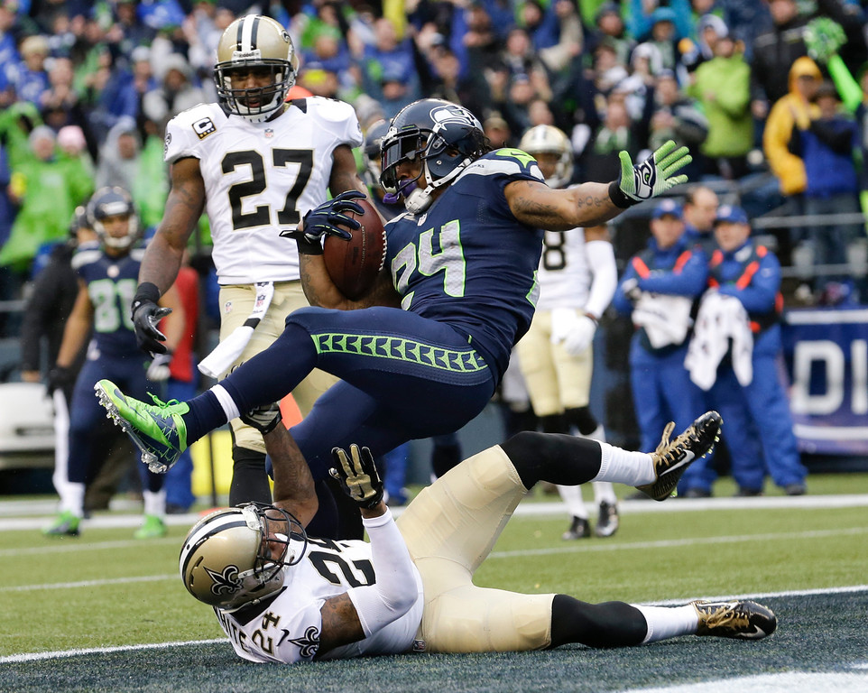 . Seattle Seahawks running back Marshawn Lynch, top, scores past New Orleans Saints cornerback Corey White (24) for a 15-yard touchdown during the second quarter of an NFC divisional playoff NFL football game in Seattle, Saturday, Jan. 11, 2014. (AP Photo/Elaine Thompson)