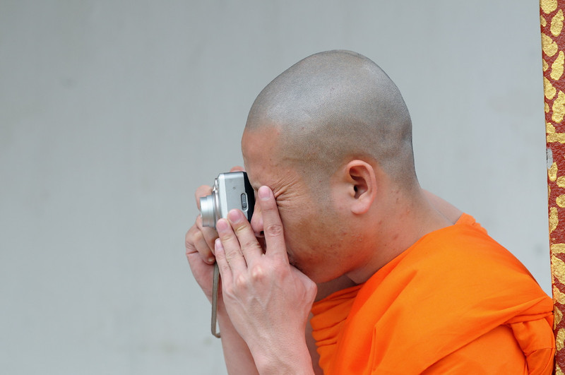 Mönch fotografiert bei den Feierlichkeiten zur Einweihung einer Stupa am Tempel im kleinen Ort Ban Naxao in der Nähe von Luang Prabang