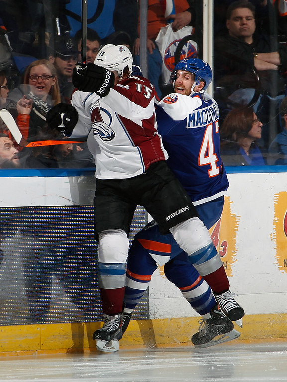 . UNIONDALE, NY - FEBRUARY 08:  P.A. Parenteau #15 of the Colorado Avalanche throws a check at Andrew MacDonald #47 of the New York Islanders  during the second period of an NHL hockey game at Nassau Veterans Memorial Coliseum on February 8, 2014 in Uniondale, New York.  (Photo by Paul Bereswill/Getty Images)